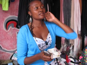 Esther Njeris, som har en bod med brugt tøj på Toi Market i Nairobi, fortæller at når hun sælger for 600 kroner tøj, så bliver de 450 af dem betalt med mobile penge. Foto: Vibeke Quaade